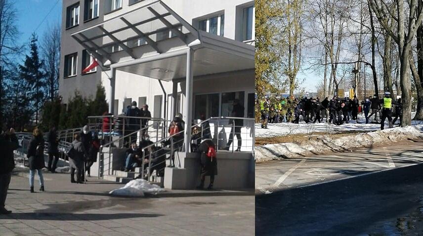 Obywatele RP czekają przed komendą policji w Hajnówce na cztery osoby, które zostały zatrzymane ponieważ nie zgodziły się na legitymowanie. Po prawej policja prowadzi do radiowozu zakutego w kajdanki z tyłu Janusza Polowczyka