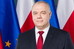 Jacek Sasin na tle flag UE i Polski