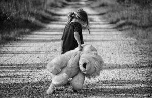 Sfotografowana odtyłu dziewczynka zidzie piaszczystą drogą. Ciągnie zasobą dużego pluszowego misia