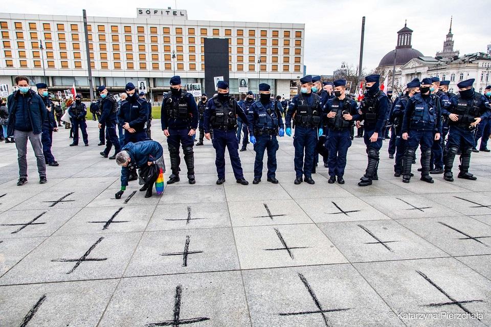 Babcie Kasia rysuje czarnym węglem krzyże na placu Piłsudskiego. Za nią stoi grupa policjantów