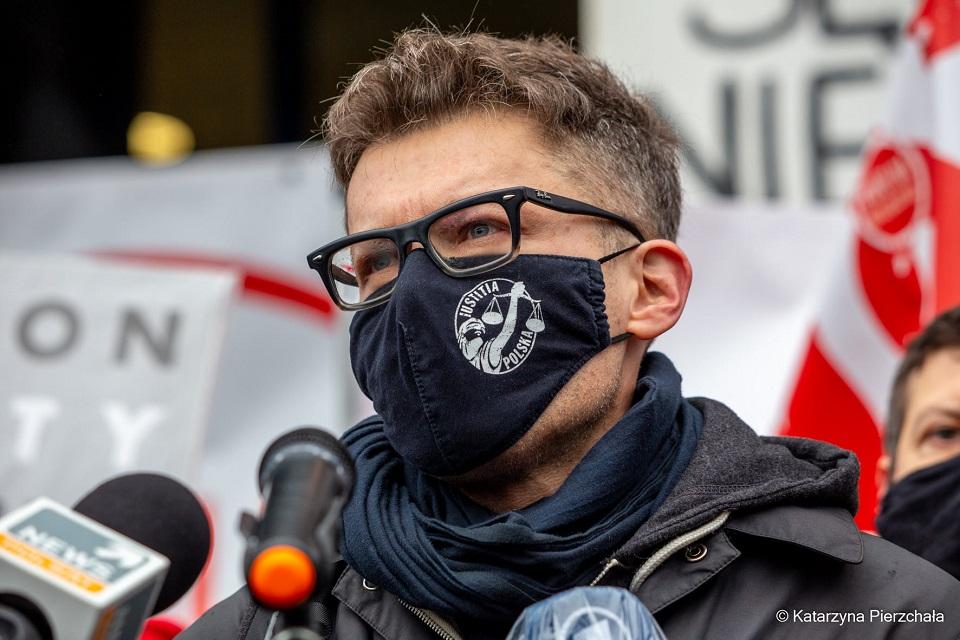 Sędzie Igor Tuleya, sfotografowany w zbliżeniu w czarnej maseczce na twarzy. Na nosie ma okulary, przed sobą mikrofony dziennikarzy