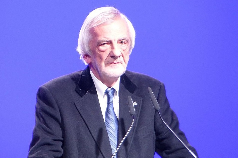 Starszy, siwy mężczyzna wgarniturze przeddwoma mikrofonami