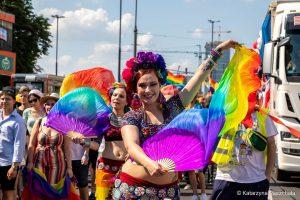 Parada Równości. Na czele dwie młode, uśmiechnięte kobiety. Na głowach mają kolorowe wianki