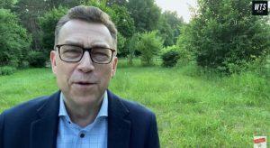 Maciej Orłoś na tle łąki i zielonych drzew
