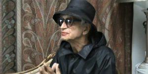 Jacek Fedorowicz w damskim kapeluszu, płaszczu i ciemnych okularach